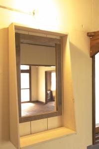 洗面。収納の扉についていた鏡に古材フローリングの枠を付けて。  Photo by Mihoko Tsujita