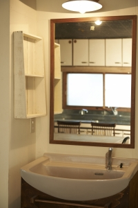 洗面スペース。玄関についていた、新築祝いの鏡に枠を付けて。棚は魚箱、照明もアンティークを加工して。  photo by MIhoko Tsujita