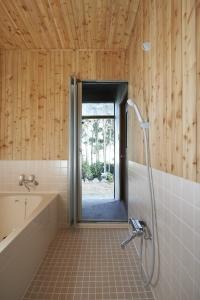 こちらは脱衣所から。外からそのままお風呂へ。唐松の板とタイルを貼りました。  photo by MIhoko Tsujita
