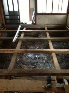 束石が固まったら、床組を作りなおします。湿気が上がってこないようにビニールシートを敷いたあと、大引を流します