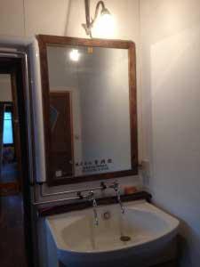 洗面台は再利用。いただいた鏡に古材の額を。